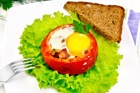 Scrambled eggs with ham and mushrooms in a tomato on a green lettuce in the plate, bread, fork and a napkin on the background light wooden boards