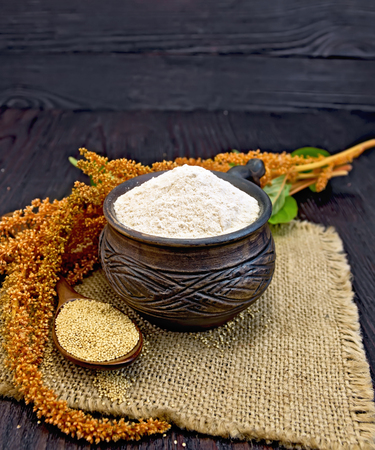 Flour amaranth in a clay cup, a spoon with grain, brown flower with green leaves on a napkin from a sacking on a background of dark wood planks