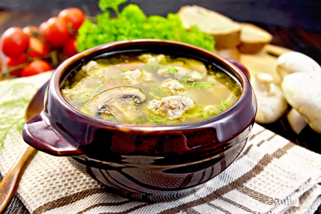 Soup with meatballs, noodles and champignon in a clay bowl, spoon on the towel, parsley, tomatoes, mushrooms and bread on a wooden boards background