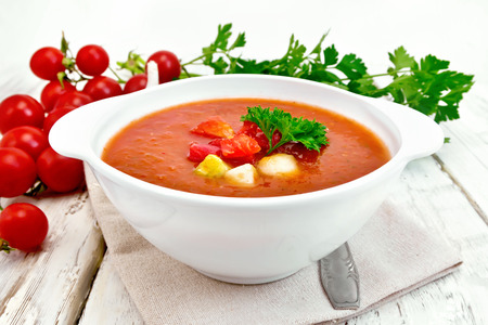 gazpacho: Gazpacho tomato soup in a white bowl with parsley and vegetables, spoon on a napkin against the background of wooden boards Stock Photo