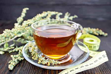 measuring cup: Herbal tea in a glass cup on a saucer, twigs gray wormwood, yellow measuring tape on the background of wooden boards
