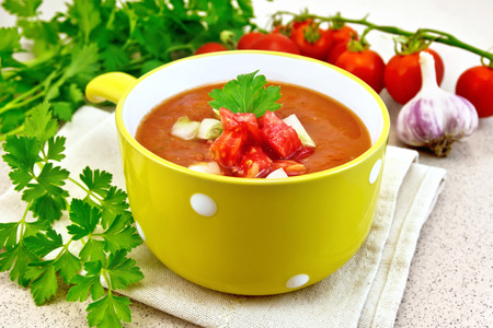 gazpacho: Gazpacho tomato soup in yellow bowl with parsley and vegetables on a napkin on the background of a granite table
