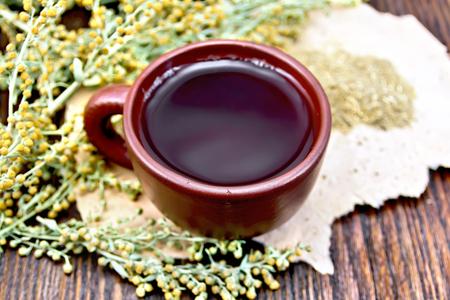 ajenjo: Herbal tea in a brown clay cup, twigs gray sagebrush, wormwood dried on rough paper on a dark wooden board Foto de archivo