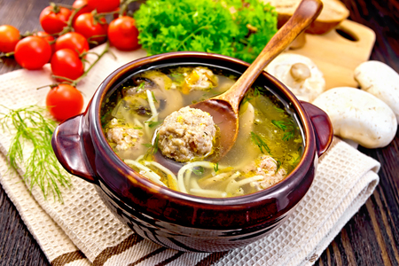 Soup with meatballs, noodles and champignon in a clay bowl with spoon on a napkin, parsley, mushrooms, tomatoes and bread on a dark wooden board
