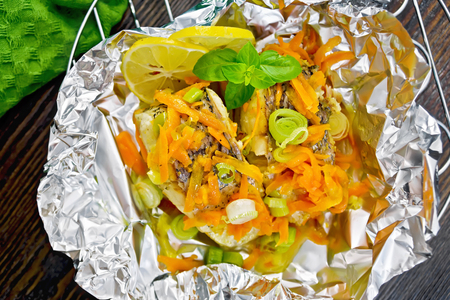 limnetic: Pike with carrots, leek, basil and slices of lemon in foil on the lattice, a towel on the background of the wooden planks on top