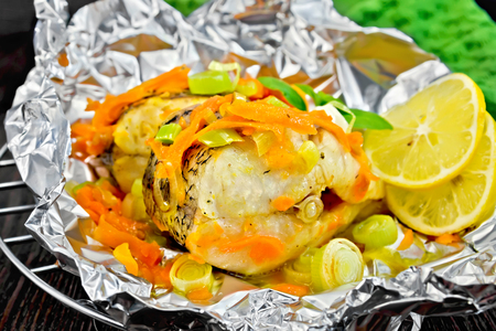 limnetic: Pike with carrots, leek, basil and slices of lemon in foil on the lattice, napkin on the background of wooden boards Stock Photo