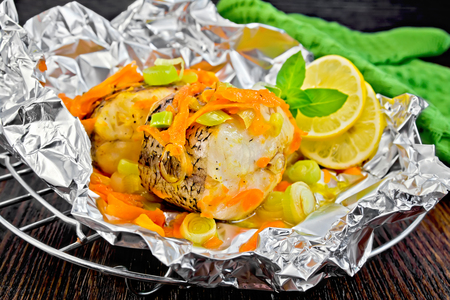 limnetic: Pike with carrots, leek, basil and slices of lemon in foil on the lattice, a napkin on the dark background of the wooden planks Stock Photo