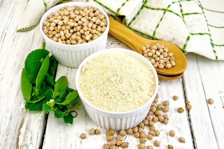 Flour chickpeas and chick-pea in white bowls and spoons, pods of green beans, a napkin on a wooden boards background