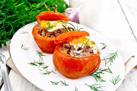 Tomatoes stuffed with meat and rice with cheese in a plate on a napkin, fork, dill and parsley on a wooden board background