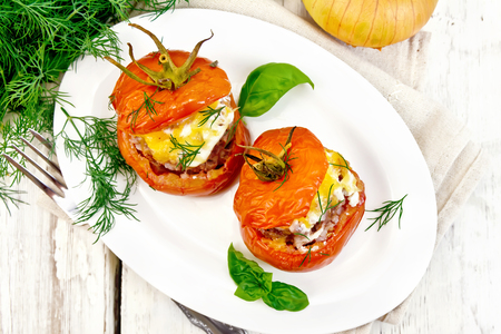 Tomatoes stuffed with meat and rice with cheese in a plate on a napkin, fork, dill and parsley on a wooden board background from above