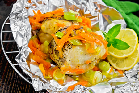 limnetic: Pike with carrots, leek, basil and slices of lemon in foil on the lattice, a towel on a background of wooden boards Stock Photo