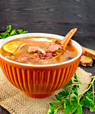 Soup saltwort with lemon, meat, pickles, tomato sauce and black olives, spoon in a sackcloth, bread and parsley on a wooden board background