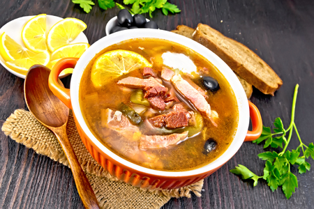 Soup saltwort with lemon, meat, pickles, tomato sauce and olives in a bowl on a sacking, bread on a background of a dark wooden board Stock Photo