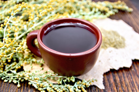 ajenjo: Herbal tea in a brown clay cup, twigs gray sagebrush, wormwood dried on a paper on the background of wooden boards