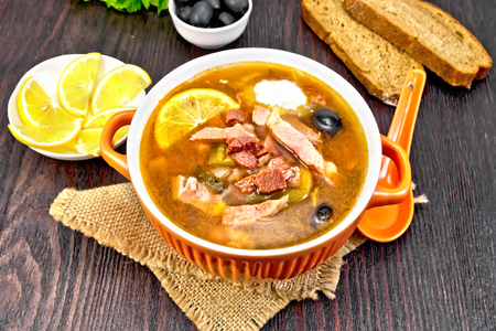 Soup saltwort with lemon, meat, pickles, tomato sauce olives in a bowl on a sacking, bread, parsley and spoon on a wooden board background Stock Photo