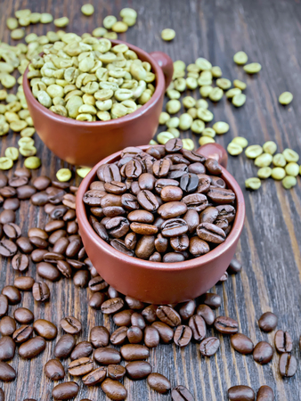Grains of green and black coffee in brown clay cups and on a table on the background of a wooden board