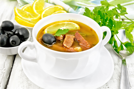 Soup saltwort with lemon, meat, pickles, tomato sauce and olives in a white bowl, towel, parsley on a light wooden board background