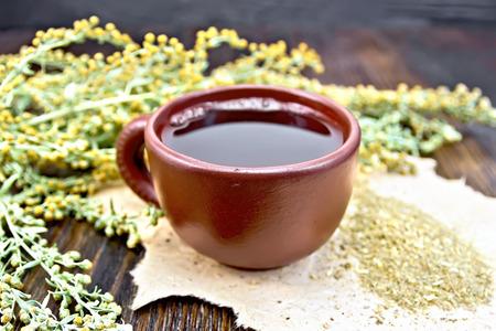 ajenjo: Té de hierbas en una taza de arcilla, ramitas artemisa gris, ajenjo secado en papel áspero en el fondo de tablas de madera Foto de archivo