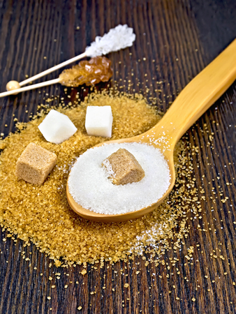 Sugar white and brown in cubes, granulated in a spoon and crystal on a stick against the background of a wooden board