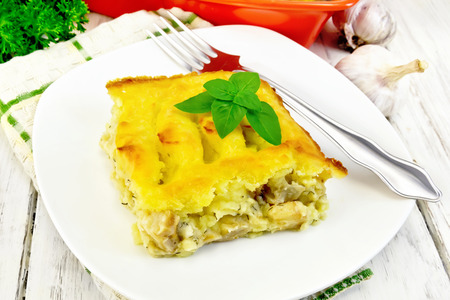 Gratin potato with fish in plate on board