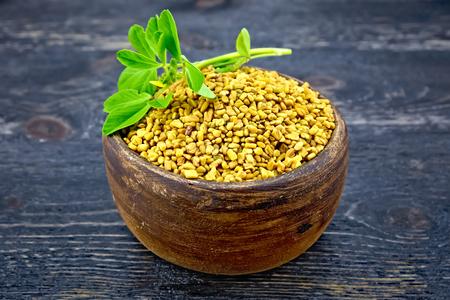 Fenugreek with leaf in clay bowl on board