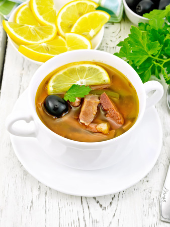 Soup saltwort with lemon, meat, pickles, tomato sauce and olives in a white bowl on a light wooden board background