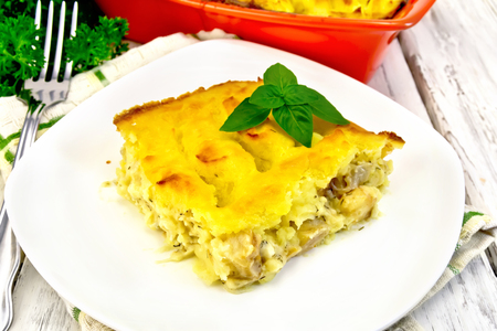 Casserole from mashed potatoes with a fish fillet in a plate on a towel on a wooden board background Stock Photo