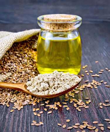 Flax flour in a spoon, oil in a glass jar, linen seeds in a bag and on a table on a background of a dark wooden board