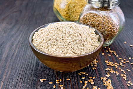 Flax flour in a bowl, white and brown linen seeds in two glass jars on a wooden board background Stock Photo