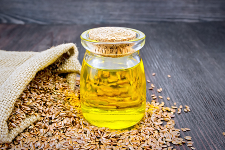 Linen oil in a glass jar with seeds in a bag and on a table on a background of a dark wooden board