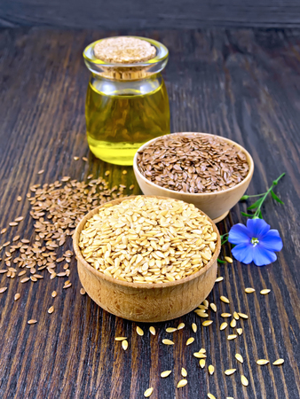 Linen seeds are white and brown in two bowls, linseed oil in a glass jar and blue flower on a wooden plank background