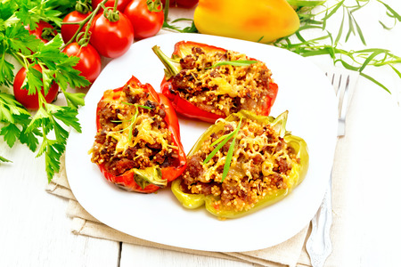 Pepper sweet, stuffed with mincemeat and couscous, cheese in a white plate on towel, a fork, tarragon and parsley against the background of wooden board Foto de archivo