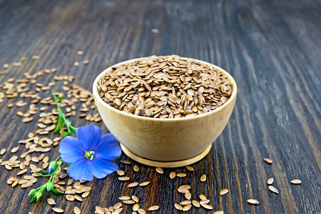 Seeds of linen brown in a bowl, blue flax flower on a wooden plank background Zdjęcie Seryjne