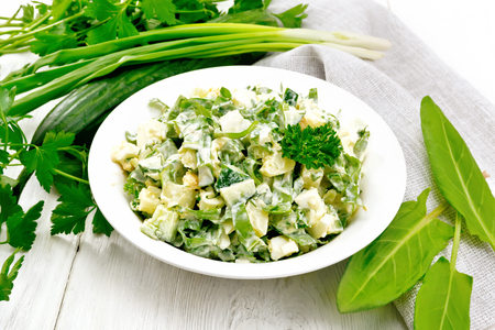 Salad of cucumber, sorrel, boiled potatoes, eggs and herbs, dressed with mayonnaise in a white plate, parsley, green onions and towel against the background of light wooden boards