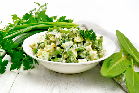Salad of cucumber, sorrel, boiled potatoes, eggs and herbs, dressed with mayonnaise in a white plate, parsley, green onions and towel against the background of wooden boards