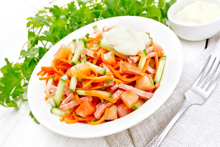 Salad from smoked sausage, spicy carrot, tomato, cucumber and spices with mayonnaise, napkin, fork and parsley on a wooden board background Stok Fotoğraf
