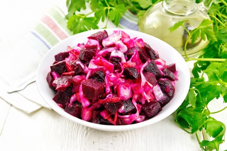 Vinaigrette salad with pickled or sauerkraut, potatoes, beetroot and onions, seasoned with vegetable oil in a bowl, napkin, parsley on the background of a light wooden board