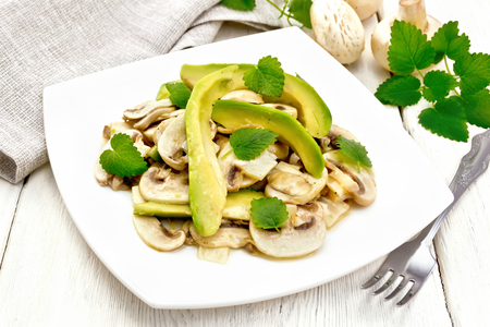Salad from avocado and raw champignons, seasoned with lemon juice and vegetable oil with mint leaves, napkin and fork on the background of a light wooden board