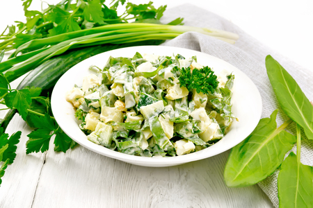 Salad of cucumber, sorrel, boiled potatoes, eggs and herbs, dressed with mayonnaise in white plate, parsley, green onions and napkin on wooden board background 版權商用圖片
