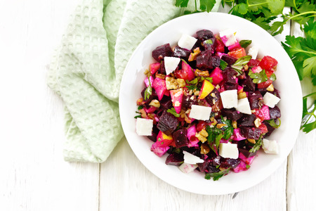 Salad with beetroot, feta cheese, apple, walnuts, parsley, seasoned with balsamic vinegar and olive oil in a plate, napkin against the background of a light wooden board on top