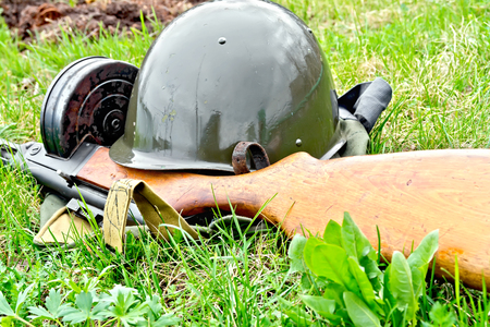 A helmet and a submachine gun of the times of the Great Patriotic War, a bag of protective color against green grass