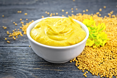 Mustard sauce in a white bowl, mustard flower and seeds on a black wooden board background