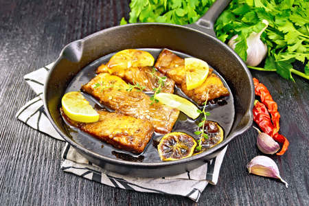 Pink salmon with honey, lemon juice, garlic, hot pepper and soy sauce, lemon slices and a sprig of thyme in frying pan on a napkin, parsley on black wooden background