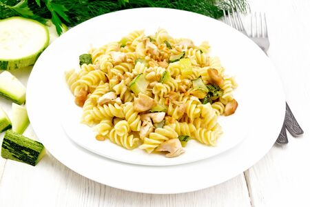 Fusilli pasta with chicken breast, zucchini, cream and pine nuts in two plates, forks and parsley on the background of a light wooden board