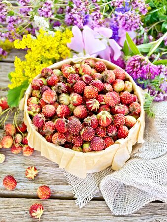 Wild ripe strawberries in a bark box with parchment, burlap and wild flowers on a wooden board background