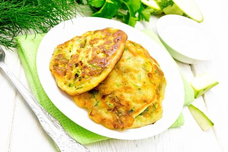 Zucchini fritters, dill and parsley in a plate on a kitchen towel, sour cream in saucer on wooden board background