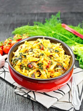 Cabbage stew with leaf beets and tomatoes in the bowl on a towel, parsley, garlic and fork on a wooden board background Stock Photo