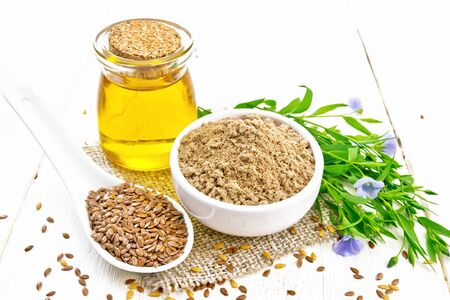 Flaxseed flour in a bowl, linenseeds in a spoon, oil in glass jar on burlap napkin, leaves and blue flaxen flowers on wooden board background
