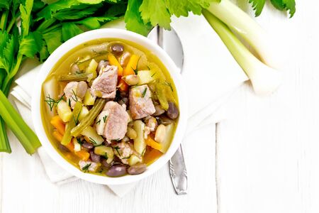 Eintopf soup of pork, celery, beans, carrots and potatoes with leek in a white bowl on a napkin on wooden board background from above