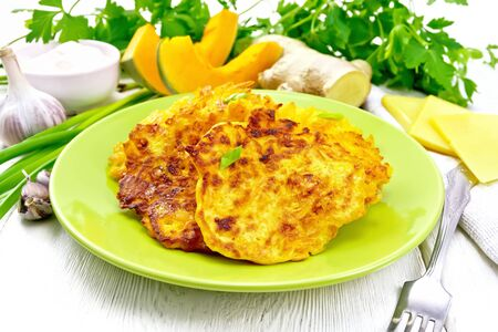 Pumpkin, cheese and ginger fritters in a green plate, sour cream in a bowl, napkin, parsley and fork on white wooden board background